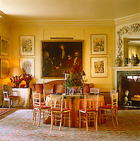 In the dining room of a town house in London a round table is surrounded by gilt Empire-style dining chairs