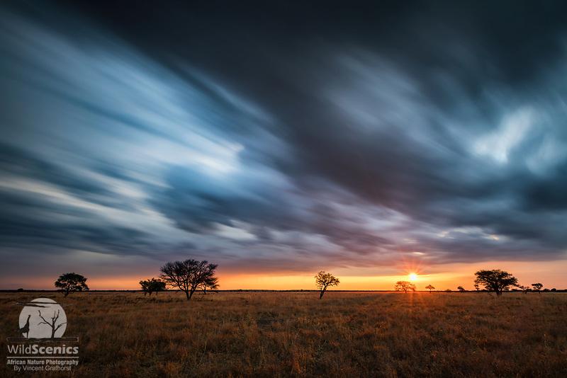 Long exposure of a moving stormy sky at sunset over a Kalahari pan.