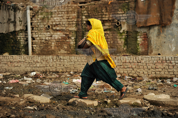 A woman walks on stepping stones over mud in a slum in the area of Nizamuddin East.