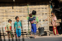 LAO PDR, province Oudomxay , village Houyta, ethnic group Khmu, boy transport water bucket with bamboo roller / LAOS Provinz Oudomxay Dorf Houyta , Ethnie Khmu , Junge transportiert Wassereimer mit Bambus Roller