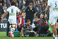 Dan Baker of Ospreys is tended to by physics after landing on his ankle after an in the air tackle from Fritz Lee of Clermont during the Champions Cup Round 1 match between Ospreys and Clermont at The Liberty Stadium, Swansea, Wales, UK. Sunday 15 October 2017