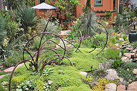 DanJohnson use a quirky sculpture made of recycled iron to set off the central area of the lower garden in his Denver backyard.