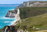 BNPS.co.uk (01202 558833)<br /> Pic: Graham Hunt/BNPS<br /> <br /> Fresh sea air and not a mask in sight over the weekend - Visitors are not put off by the coronavirus pandemic and flock to Lulworth Cove on the Dorset Jurassic Coast on a sunny afternoon.<br /> <br /> Visitors walking along the South West Coast Path between Lulworth Cove and Durdle Door with a view towards Swyre Head and Bats Head.