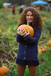 Portrait of a young smiling woman holding a pumpkin at a farm pumpking patch, British Columbia, Canada, autumn harvest