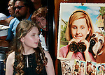 US actress Abigail Breslin looks at herself in the poster as she arrives at the world premiere of 'Kit Kittredge: An American Girl' at the Grove in Los Angeles, California on 14 June 2008. The film is based on the American Girl doll line and centers on Kit Kittredge, a young woman who grows up in the early years of the Great Depression.