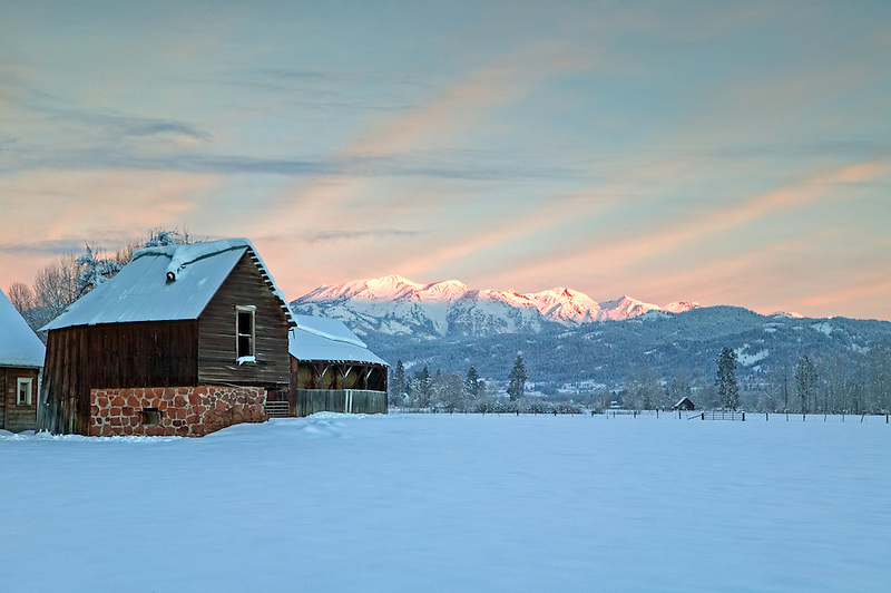 Abandoned farmhouse with snow and Wallowa Mountains. Halfway, Oregon