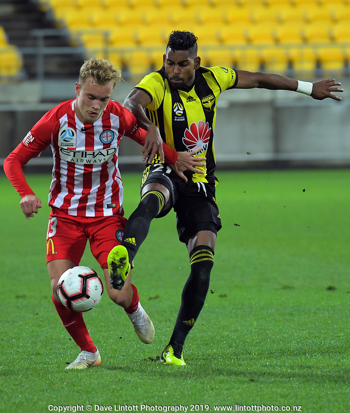 Roy Krishna (right) tries to tackle Nathaniel Atkinson during the A-League football match between Wellington Phoenix and Melbourne City FC at Westpac Stadium in Wellington, New Zealand on Sunday, 21 April 2019. Photo: Dave Lintott / lintottphoto.co.nz