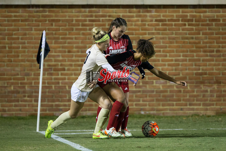 Bayley Feist (9) of the Wake Forest Demon Deacons battles for the ball with Gabrielle Vincent (14) and Shelby Cohen (4) of the Louisville Cardinals during second half action at Spry Soccer Stadium on October 31, 2015 in Winston-Salem, North Carolina.  The Demon Deacons defeated the Cardinals 2-1.  (Brian Westerholt/Sports On Film)