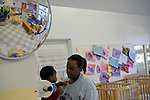 Teacher Donna Powell, 29, changes Eddie Washington, 11 months, at the Educare Early Childhood Center in Chicago on November 21, 2008.  The pre-K daycare center is a model for head start, funded privately by the Gates and other foundations, that cares for and educates infants, toddlers, and 3- and 4-year old pre-school children.