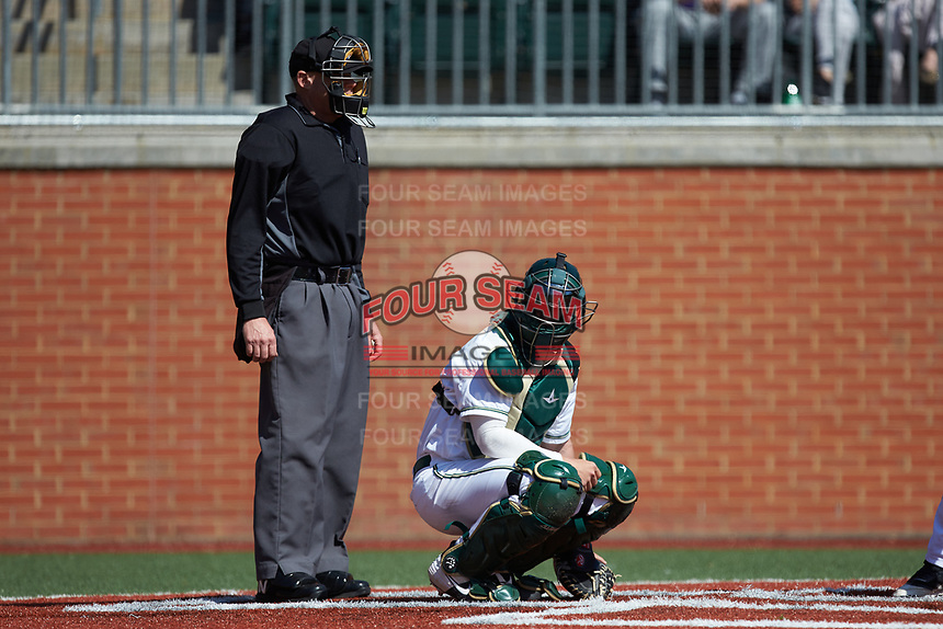Charlotte 49ers catcher Craig Keuchel (9) looks to the dugout for the sign as home plate umpire Richie Hogg looks on during the game against the East Carolina Pirates at Hayes Stadium on March 8, 2020 in Charlotte, North Carolina. The Pirates defeated the 49ers 4-1. (Brian Westerholt/Four Seam Images)