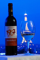 Bottle of 1907 Madiran Fruit and Passion against a dark blue background sky view over Paris with the Eiffel Tower and a glass of wine with a reflection Madiran France