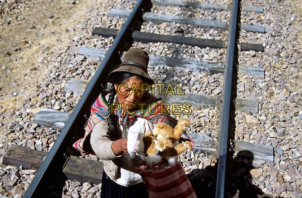 Lady selling toys on railway track, La Raya, Puno to Cusco Perurail train journey, Peru