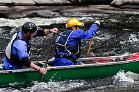 Two men paddling an open canoe in the Hudson White Water Derby in the Adirondack Forest Preserve in New York