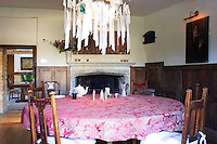 In the panelled dining room a home-made chandelier of paper streamers containing hand-written messages from friends hangs above the large round table which is covered with a burgundy damask cloth
