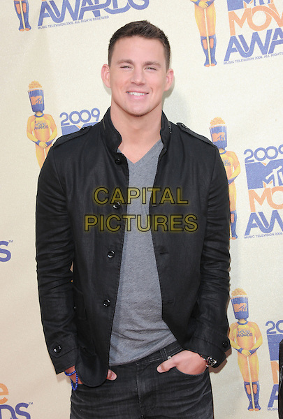 CHANNING TATUM.The 2009 MTV Movie Awards held at Universal Ampitheatre  in Universal City, California, USA..May 31st, 2009  .half length grey gray top black jacket hands in pockets .CAP/DVS.©Debbie VanStory/Capital Pictures.