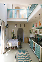 The double-height living area of the Casita is furnished in a palette of turquoise, off-white and black