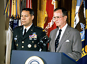 United States President George H.W. Bush and first lady Barbara Bush present the Presidential Medal of Freedom to Chairman of the Joint Chiefs of Staff US Army General Colin L. Powell during a ceremony in the East Room of the White House in Washington, DC on July 3, 1991. General Powell is being honored for his efforts to ensure the success of Operation Desert Shield / Operation Desert Storm and the liberation of Kuwait.<br /> Credit: Ron Sachs / CNP