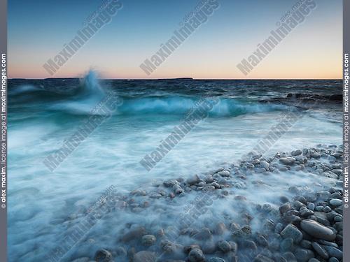 Beautiful sunrise nature scenery of waves hitting the shore of Georgian Bay in stormy weather. Bruce Peninsula National Park, Ontario, Canada.