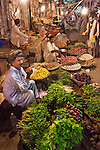 A photo of a street vendor smoking a cigarette and selling vegetables at night in the old bazaar in Rawalpindi in Pakistan