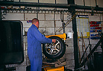 A08ATC Mechanic fitter repairing tyre puncture in garage workshop