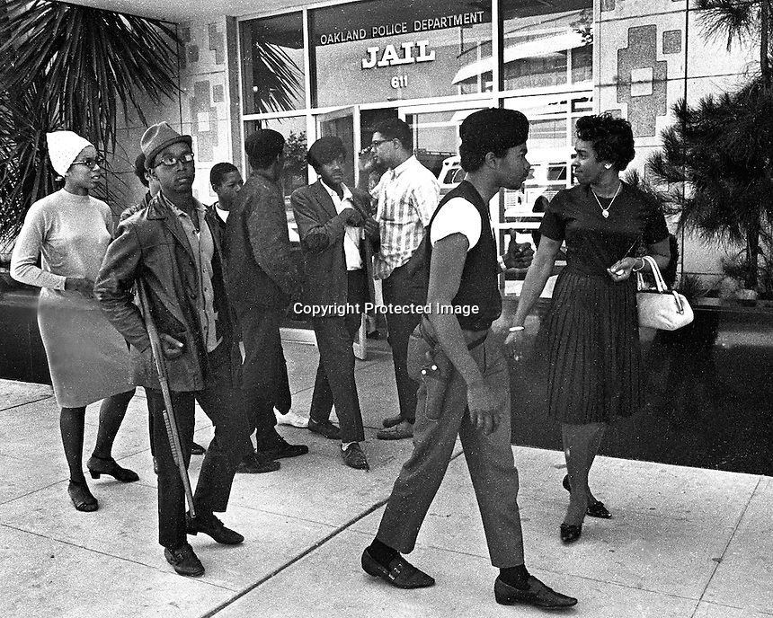 Black Panthers Bobby Hutton, Bobby Seale and others gather in front of the Oakland,Ca Police Dept Jail entrance. May 23,1967. Hutton with shotgun was killed months later in shootout with Oakland Police.<br />