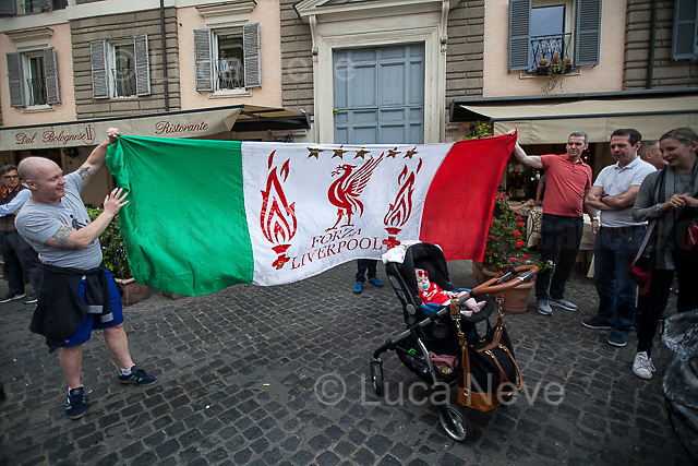 Piazza del Popolo.<br /> <br /> Rome, 02/05/2018. Following and documenting a group of Liverpool F.C. supporters chanting and cheering on throughout the streets of central Rome while waiting for the Champions League Semi-final (second leg) at the Stadio Olimpico versus A.S. Roma. The supporters were escorted by heavy presence of the Italian Police and Carabinieri, assisted by Merseyside Police's officers (British Police) and by the stewards and staff from Liverpool Football Club. Last week, during the first leg of the semi-final in Liverpool, an English fan was attacked by Italian supporters outside Anfield stadium. However, the day of the match in Rome passed without any serious incidents involving supporters and just one arrest - a Liverpool supporter - was made (on suspicion of common assault and a public order offence). The actual match was played in the evening and saw Liverpool losing 4-2 but due to the aggregate with the first match, 7-6, the &quot;Reds&quot; conquered the access to the Champions League final in Kiev against Real Madrid. A statement from the English club read: &quot;Liverpool would like to thank all supporters who travelled to Rome for Wednesday evening's Champions League meeting with Roma at Stadio Olimpico for their exemplary conduct. Over 5,000 fans made the journey to the Italian capital for yesterday's semi-final second leg, behaving impeccably throughout, with no major incidents reported. LFC also acknowledges the significant resources deployed by Roma, UEFA, Merseyside police, Italian police and security services in Rome to ensure all fans enjoyed a safe visit.&quot;<br /> <br /> For more info about the football teams please click here: http://www.asroma.com/en &amp; http://www.liverpoolfc.com/