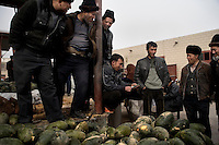 Men look over melons for sale in a small market in Kashgar, Xinjiang, China.