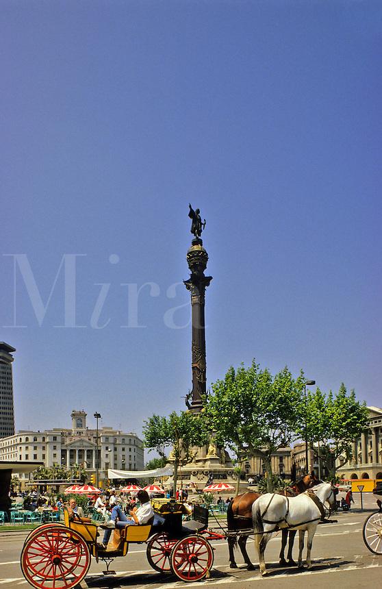 Barcelona, Spain.  Statue of Columbus in Placa del Portal de la Pau and horsedrawn carriage.