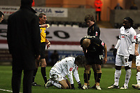Pictured: Referee Steve Tanner (L) showing Aron Gunnarsson (2nd R) of Coventry City a yellow card for his foul against Jordi Gomez of Swansea City who is on the ground while Leon McKenzie of Coventry seems to be bending down to vent his anger to Gomez.<br /> Re: Coca Cola Championship, Swansea City FC v Coventry City at the Liberty Stadium. Swansea, south Wales, Friday 26 December 2008.<br /> Picture by D Legakis Photography / Athena Picture Agency, Swansea 07815441513