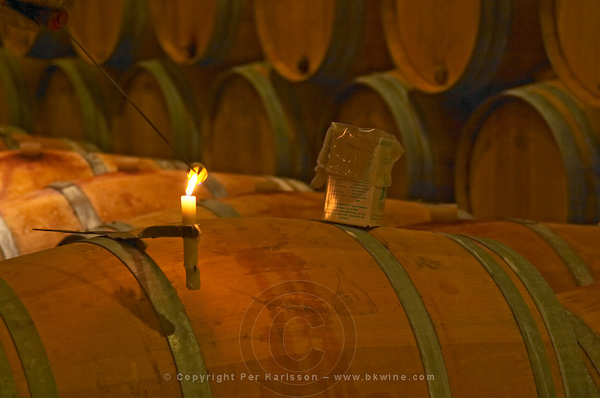 The winery, barrel aging cellar: a burning candle, a box of sulphur pellets and a winery worker lighting a pellet of sulphur to clean a barrel - Chateau Baron Pichon Longueville, Pauillac, Medoc, Bordeaux, Grand Cru