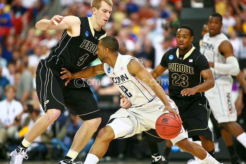 Mar 26, 2009; Tucson, AZ, USA; Connecticut Huskies guard A.J. Price (12) is defended by Purdue Boilermakers forward Robbie Hummel (4) and guard Lewis Jackson (23) in the first half of a game during the semifinals of the west region of the 2009 NCAA basketball tournament at University of Phoenix Stadium.