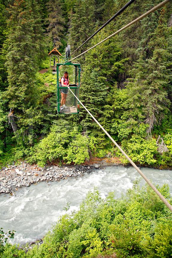 A hiker pulls herself across Glacier Creek on the aerial hand tram, Winner Creek Gorge Trail, Girdwood, Chugach National Forest, Alaska.