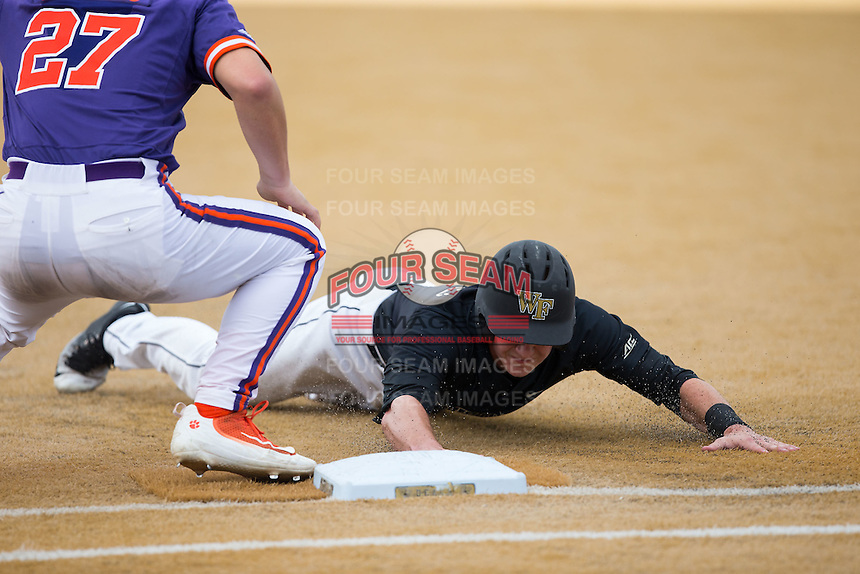 Drew Freedman (5) of the Wake Forest Demon Deacons dives back into first base during the game against the Clemson Tigers at David F. Couch Ballpark on March 12, 2016 in Winston-Salem, North Carolina.  The Tigers defeated the Demon Deacons 6-5.  (Brian Westerholt/Four Seam Images)
