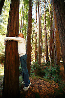 Blair Crowder hugs a Redwood Tree  in Pfeiffer Big Sur State Park, California. The park is located off of the famously scenic Highway One in Big Sur.