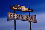 A view on a moonlit night of the sign for the abandoned Road Runner's Retreat Restaurant, located along historic Route 66, near Chambless, California