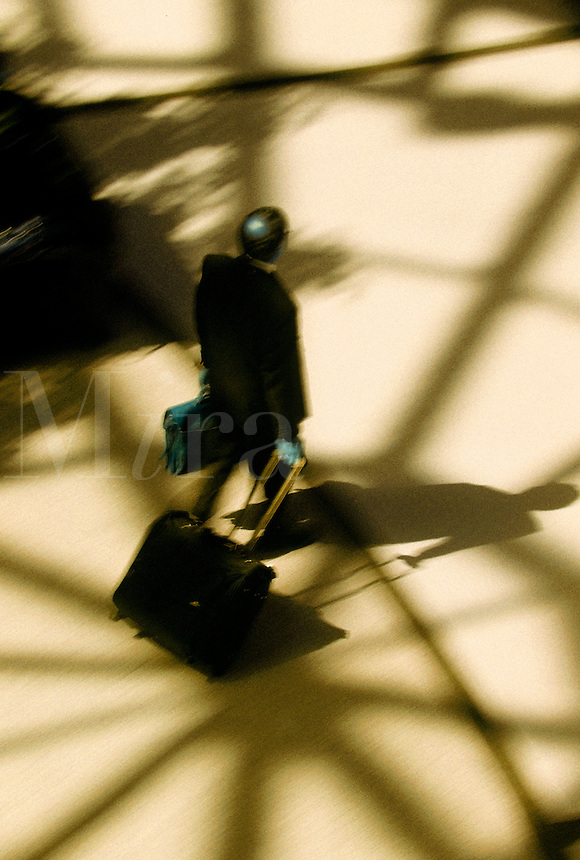 Overview of a business traveller and shadow as he transports a suitcase across a patterned floor.