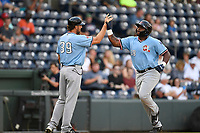 First baseman Tyreque Reed (38) of the Hickory Crawdads high-fives manager Matt Hagen (39) after hitting a three-run home run in the first inning of a game against the Greenville Drive on Monday, August 20, 2018, at Fluor Field at the West End in Greenville, South Carolina. Hickory won, 11-2. (Tom Priddy/Four Seam Images)