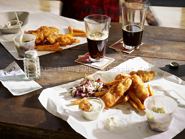 Two orders of fish & chips and beers at a pub.
