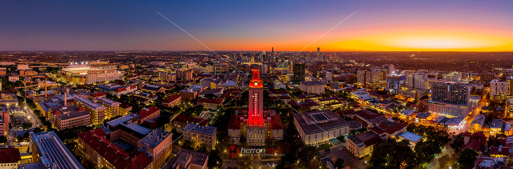 Aerial view of the UT Tower emblazoned with with No. 1 lights on after a national championship victory, looking at the Texas Tower south at sunrise in this aerial photograph, you can see the well known downtown Austin buildings in the distance including the Darrell K Royal Texas Memorial Stadium, UT Forty Acres campus, Guadalupe Street UT drag, Texas Capitol, the Frost Tower, Austonian, and the Independent Austin Jenga Tower.