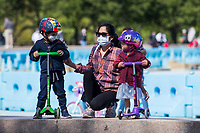 NEW YORK, NY - MAY 10: A woman in the company of two children wearing face masks stands in front of Circle Fence at Flushing Meadows-Corona Park on Mother's Day on May 10, 2020 in Queens, NY. COVID-19 has spread to most countries in the world, claiming more than 283,000 lives and more than 4.1 million people infected, Queens has been one of the places most affected by the Coronavirus. (Photo by Pablo Monsalve / VIEWpress via Getty Images)