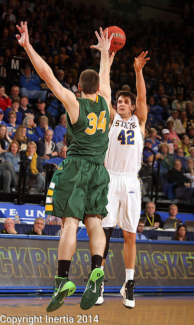 BROOKINGS, SD - JANUARY 25:  Jordan Dykstra #42 from South Dakota State University spots up for a jumper over Chris Kading #34 from North Dakota State University in the first half of their game Saturday afternoon at Frost Arena in Brookings. (Photo by Dave Eggen/Inertia)