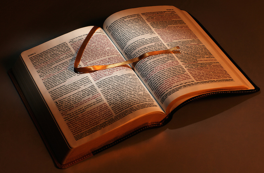 A bright light shines across the pages of a Christian Bible with a gold-colored bookmark.