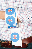 A supporter of Democratic presidential candidate Hillary Clinton holds a roll of stickers for attendees outside St. Geogre Greek Orthodox Cathedral during the annual New Hampshire AFL-CIO Labor Day Breakfast in Manchester, New Hampshire.