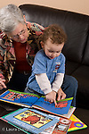 2 year old toddler boy at home with grandmother interaction read to from picture book boy pointing to illustration language development vertical she takes care of him when parents work
