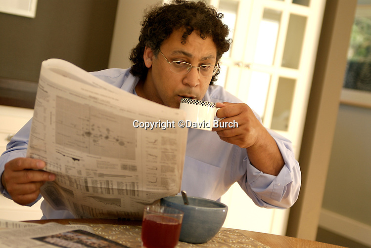 Man with cup of coffee reading newspaper at breakfast