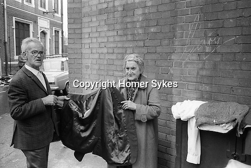 Couple buying selling second hand clothes. Checking a mans jacket. Tower Hamlets, East London UK 1978