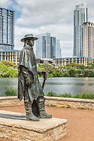 Stevie Ray Vaughan statue on Ladybird Lake with the Austin skyline in the backrground along the hike and bike trail is an Austin iconic site. Everyone stop to catch a photo from this location.