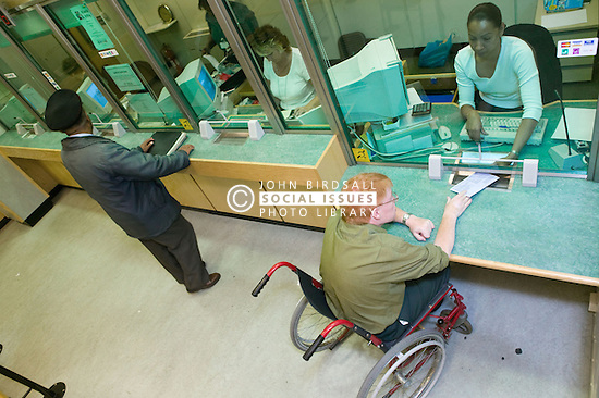 Man who is a wheelchair user paying his council tax bill at an accessible low level desk,