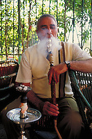 man smoking water pipe in restaurant