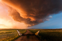 Colorful supercell thunderstorm above a dirt road at sunset in Montana, May 18, 2014